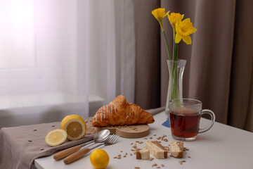 Breakfast with a cup of tea, croissants, lemons and yellow narcis in a glass vase