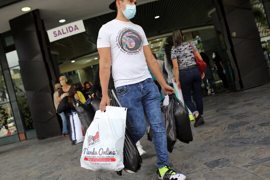 A man leaves a mall with shopping bags during the Black Friday sales in Caracas