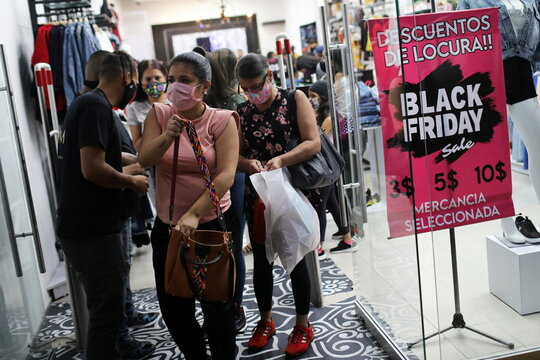 People leave a shop at a mall during the Black Friday sales in Caracas