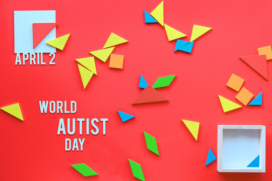 Creative design for Autism World Day on April 2. Colorful tangram wood elements scattered on red.