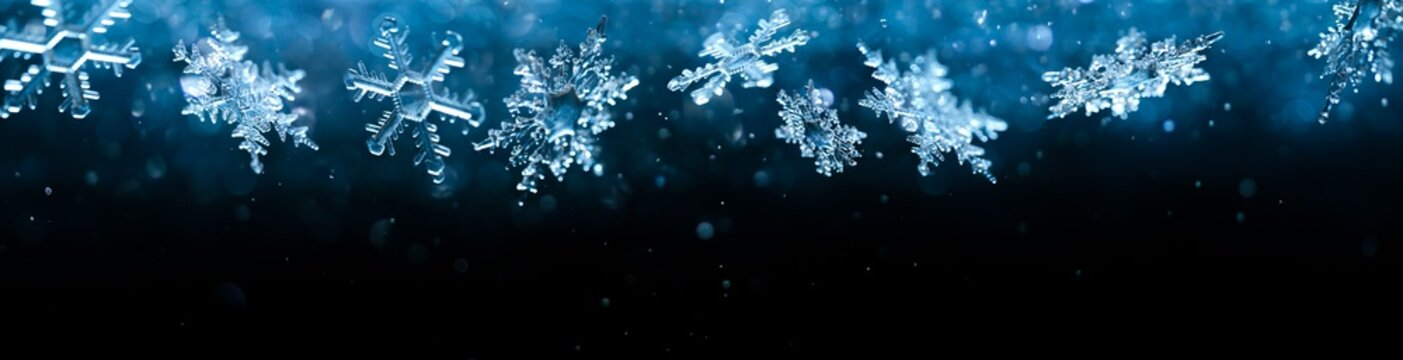 Cold winter snowflakes falling with sparkling falling snow and glittering blue background.