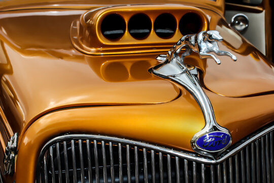 Brisbane, Queensland, Australia - July 14, 2013: Close up view of a gold Ford V8 pickup hot rod car bonnet, showing a greyhound hood ornament. This model was launched between 1932 and 1934.