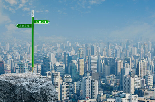 2021 and 2020 direction sign plate with green pencil on rock mountain over modern city tower, office building and skyscraper, Business strategy planning concept, Happy new year 2021 calendar cover
