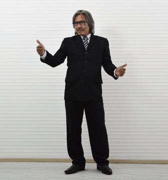 Cheerful elderly asian businessman in black suit and eyeglasses making thumbs up standing over white wall background, Business confident and success concept
