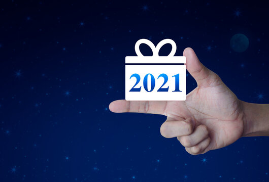 Gift box happy new year 2021 flat icon on finger over fantasy night sky and moon, Business shopping online concept