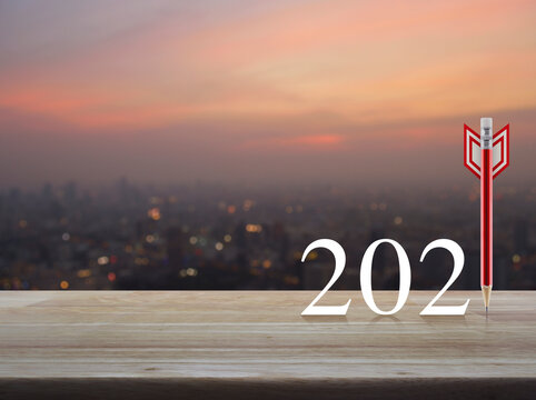 Red pencil in the shape of a dart with 2021 white text on wooden table over blur of cityscape on warm light sundown, Business strategy happy new year 2021 cover concept