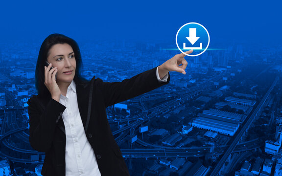 Caucasian businesswoman talking on her cell phone and pointing to download flat icon standing over modern city tower, street and expressway, Technology internet online concept