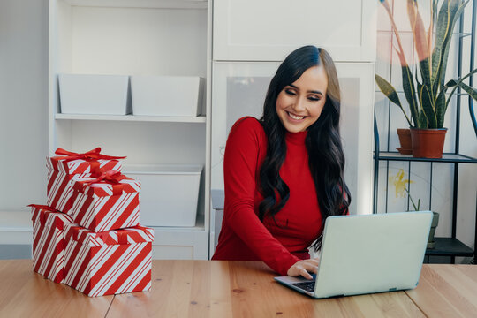 Portrait of a smiling young woman buying Christmas gifts online at home