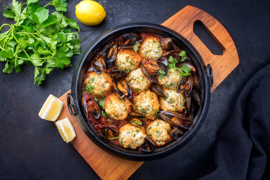 Traditional Norwegian fish ball fiskeboller with fish and mussels in red wine sauce as top view in a modern design pot