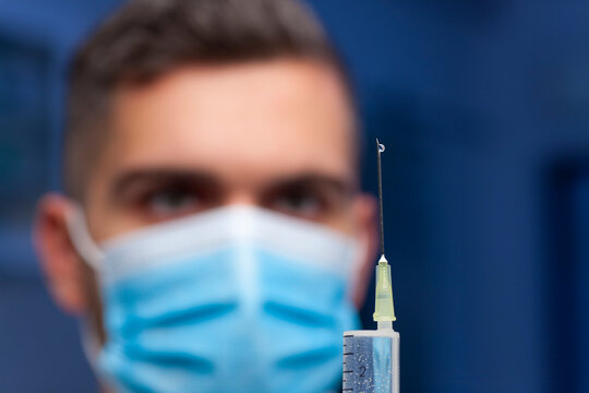 Close-up of doctor with medical mask preparing a syringe for vaccination against covid-19