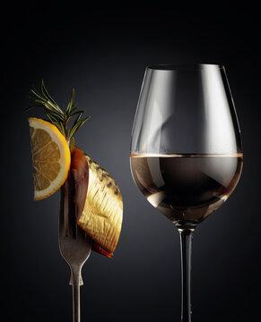 Glass of white wine and smoked mackerel with lemon slice.