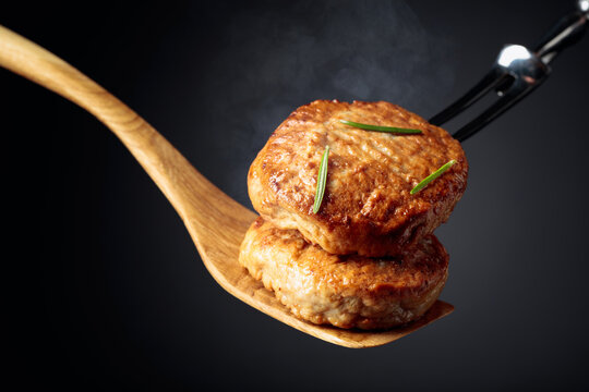 Delicious hot homemade cutlets with rosemary on a black background.