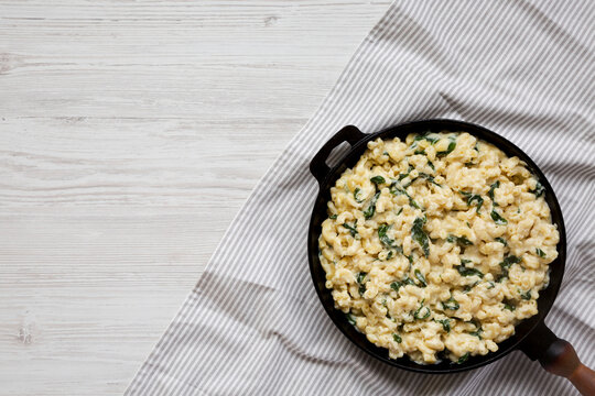 Homemade Spinach Mac and Cheese in a cast-iron pan on a white wooden background, top view. Flat lay, overhead, from above. Copy space.