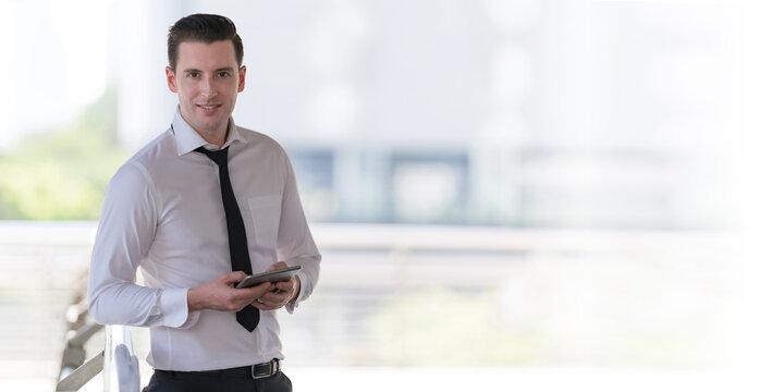 Portrait of smiling businessman using at tablet