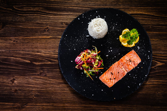 Oven baked salmon steak with white basmati rice,  lemon and fresh vegetable salad served on black stone plate on wooden table
