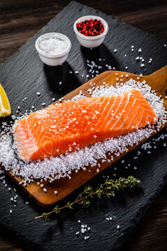 Fresh raw salmon steaks with salt on wooden board