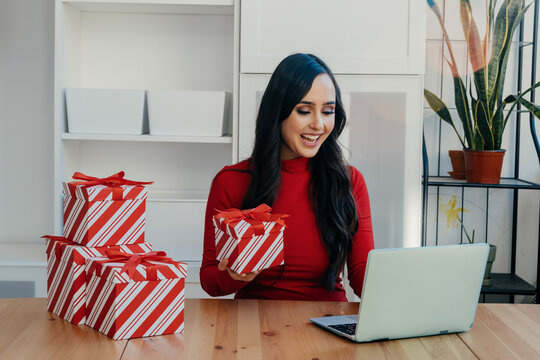 Portrait of a smiling young woman celebrating Christmas opening gifts while talking to family online at home