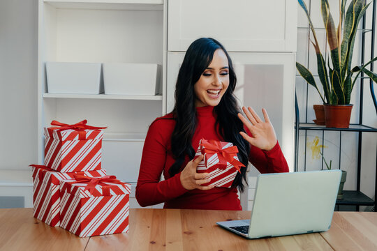 Portrait of a smiling young woman celebrating Christmas opening gifts connected to family online at home