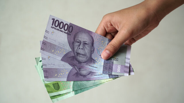 Indonesian rupiah currency, 10,000 rupiah and 20,000 rupiah, is held by women's hands