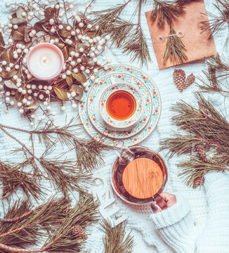 Winter and Christmas lifestyle. Woman hand holding tea pot on white knitted blanket with cup of tea, Christmas wreath and fir cones and branches. Top view