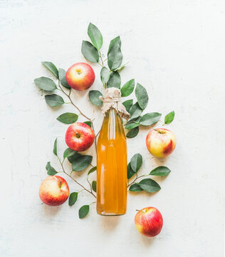 Homemade apple vinegar in glass bottle with apples and green leaves on white background. Top view