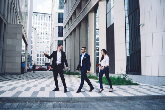 Confident colleagues walking along pavement
