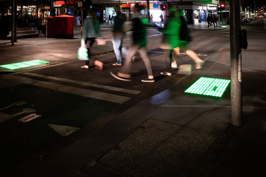 Anonymous shoppers crossing a city road at night in the city