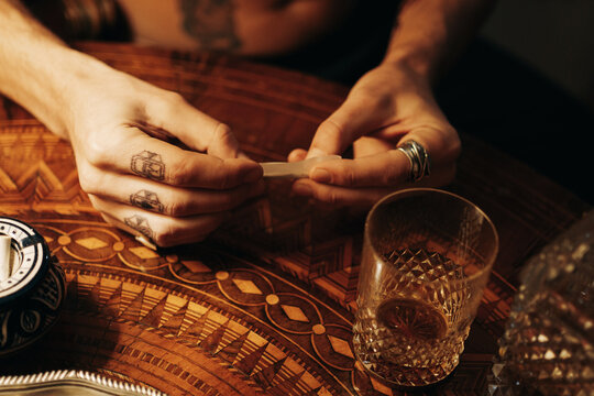 Anonymous Man With Finger Tattoos Rolling A Joint