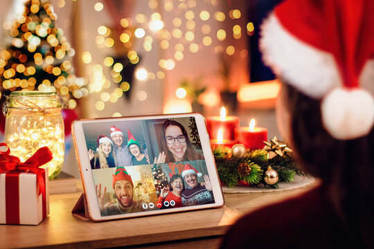 Young woman having a Christmas video call with her happy family. Concept of families in quarantine during Christmas because of the coronavirus. Xmas still life with a tablet in a cozy room