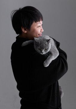 Asian woman hugging cute pet cat, indoors