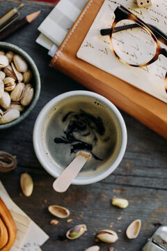 Black coffee cup on wooden table close to agenda and pistachio bowl