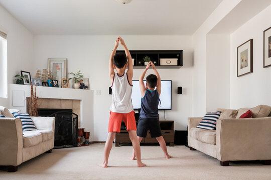 Asian Kids Exercising at Home
