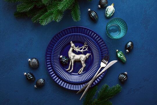 Christmas festive dinner table setting in dark blue tones