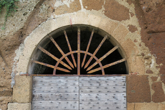 arch with a metal grate above a wooden door in a stone wall