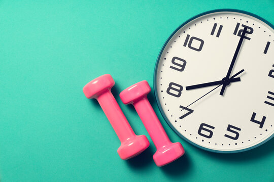 Time for exercising clock and dumbbell with green yoga mat background, sport and healthy concept