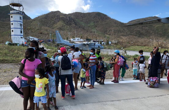 Women and children affected by the passage of storm Iota line up to board an evacuation flight to San Andres, in Providencia