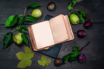 Old open book next to plums and pears on a wooden table