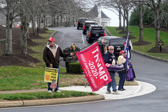 Supporters of U.S. President Donald Trump watch as he arrives at the Trump National Golf Club in Sterling, Virginia