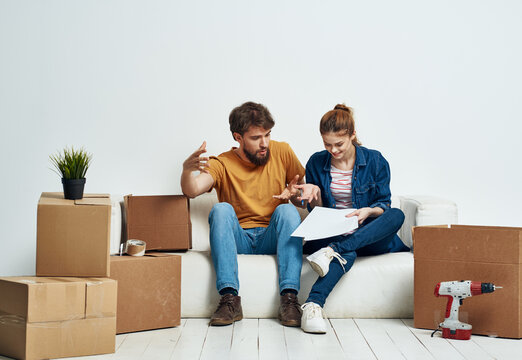 Man and woman in new room stuff in boxes moving family interior