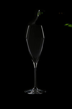 Cold Air Seen Escaping a Bottle of Champagne Just About to be Poured into a Crystal Glass Isolated on Black Background