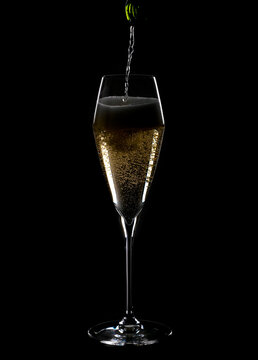 Pouring Champagne into a Lead Crystal Flute Back Lit and Isolated on Black Background
