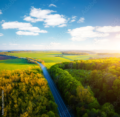 Wall mural Scenic aerial photography of rural road passing through agricultural land and green fields. Top view drone shot.