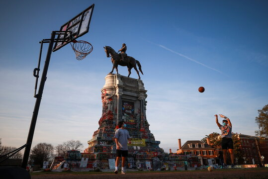 People play basketball on a hoop set up at the base of the monument to Confederate General Robert E. Lee, in Richmond, Virginia