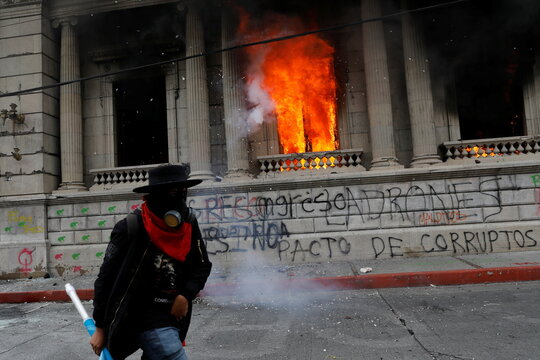 Demonstrators are seen after setting on fire an office of the Congress building during a protest demanding the resignation of President Alejandro Giammattei, in Guatemala City