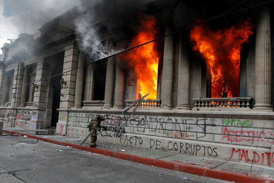 A firefighter works on the Congress building, set on fire by demonstrators during a protest demanding the resignation of President Alejandro Giammattei, in Guatemala City