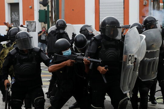 Riot police react to demostrotors during a protest demanding the resignation of President Alejandro Giammattei, in Guatemala City