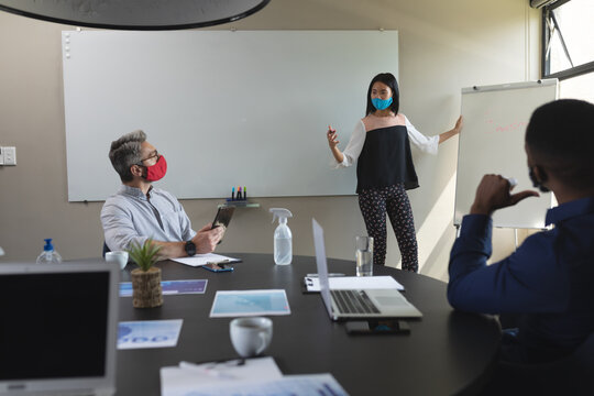Asian woman wearing face mask giving presentation to diverse colleagues in meeting room at modern of