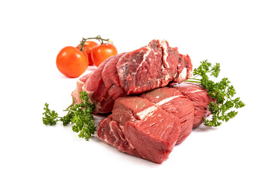 Two pieces of beef sirloin tip roast with tomatoes and parsley garnish isolated on white