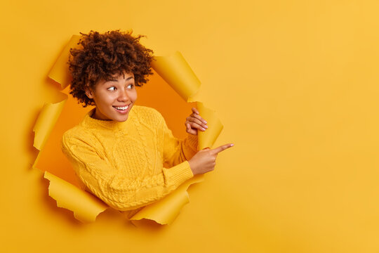 Try this! Cheerful pleasant looking young Afro American woman points away on copy blank space dressed in casual jumper breaks through paper wall gives recommendation asks to use good opportunity