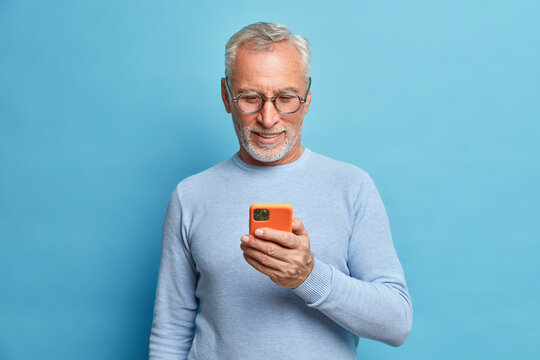Photo of satisfied bearded man focused in smart phone surfs internet sends text messages in social networks uses modern technologies wears casual blue jumper poses indoor. Senior freelancer.